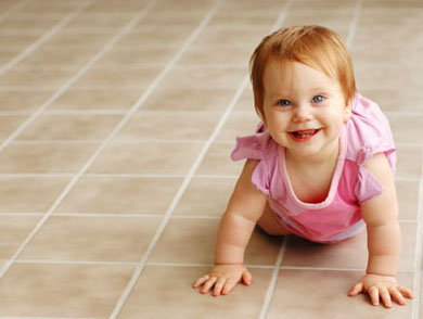 Baby crawling across freshly cleaned tile