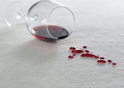 A glass of wine spills on the carpet